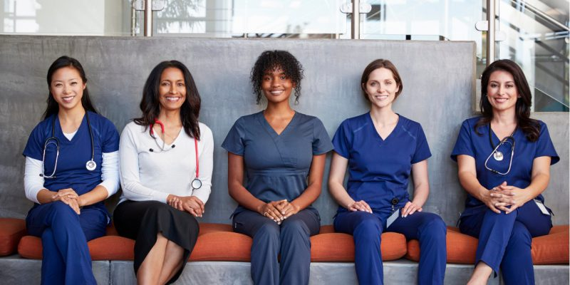 Female Nurses Sitting on Bench Waiting